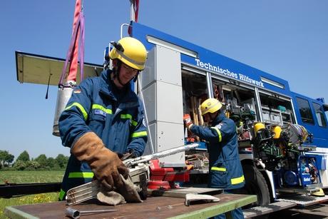 THW-Kräfte bereiten sich vor dem Gerätekraftwagen auf den nächsten Einsatz vor.